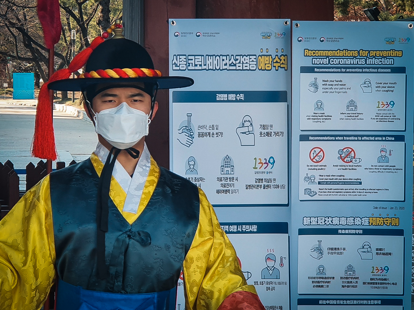 A guard in front of a traditional palace in Seoul wears a mask and stands in front of signs for recommendations for preventing the spread of the Coronavirus.